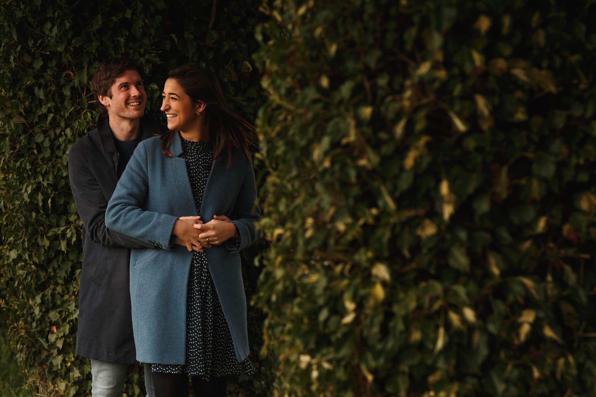 couple stood under bushes on photo shoot