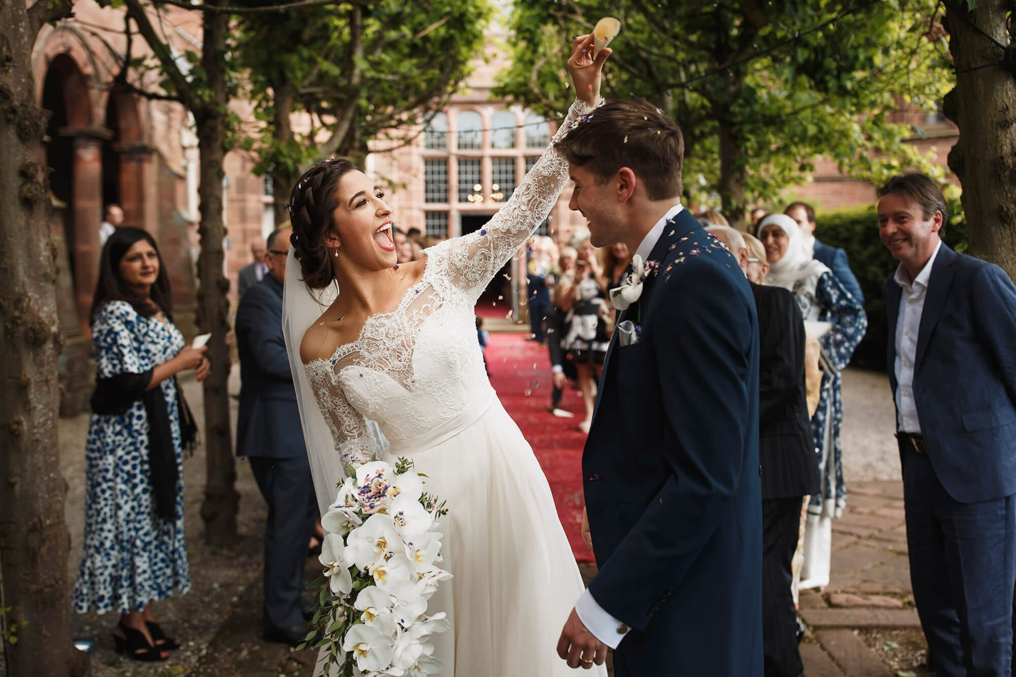 Bride throwing confetti on groom Thornton Manor House